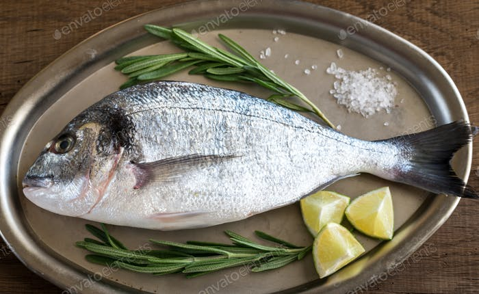 Fresh dorada with ingredients on the vintage tray