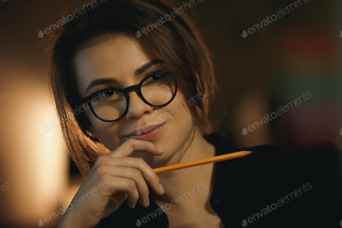 Concentrated young lady designer holding pencil.