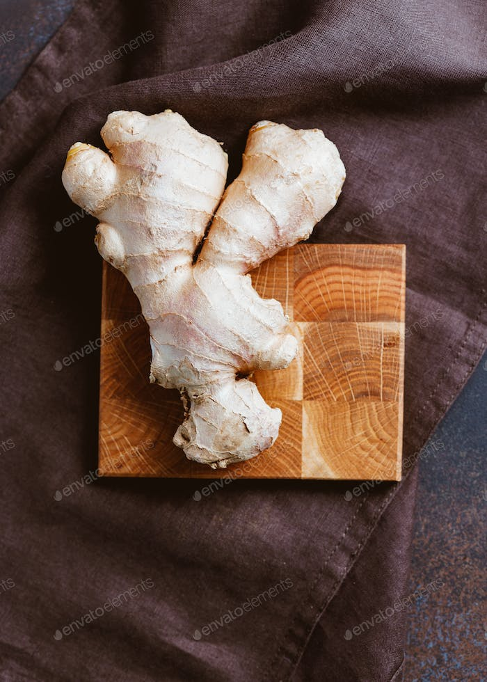 Top view of a ginger root on a wooden board.