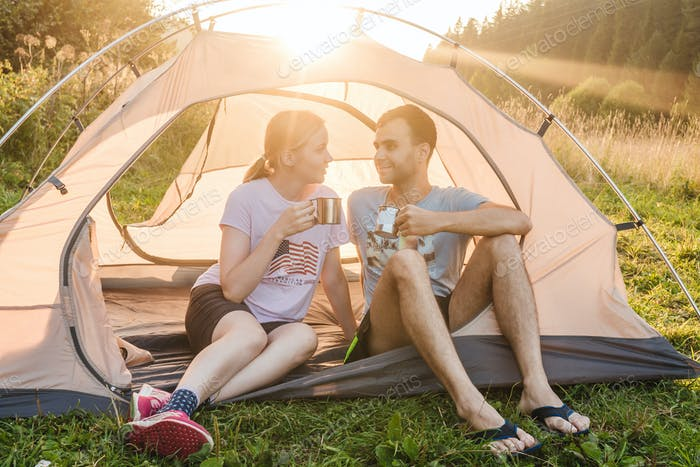 Young couple in tent drink tea, camping.