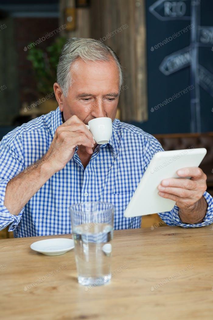 Senior Mann mit Tablet-Computer, während Kaffee trinken