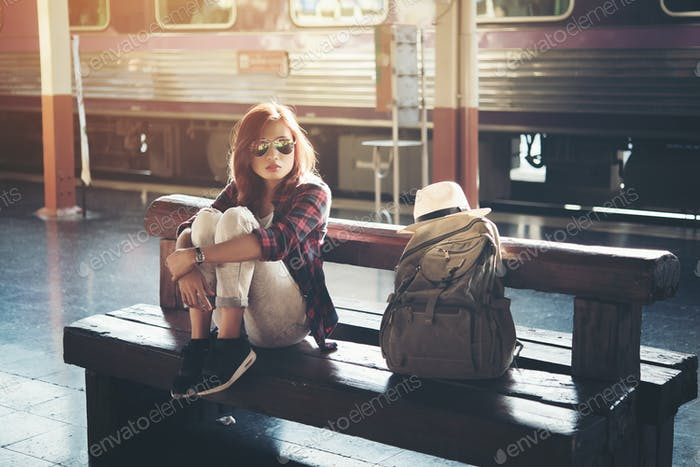 Hipster woman backpacking sitting at the train station