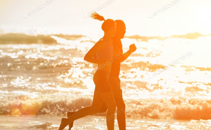 Fitness couple running along the beach during sunset