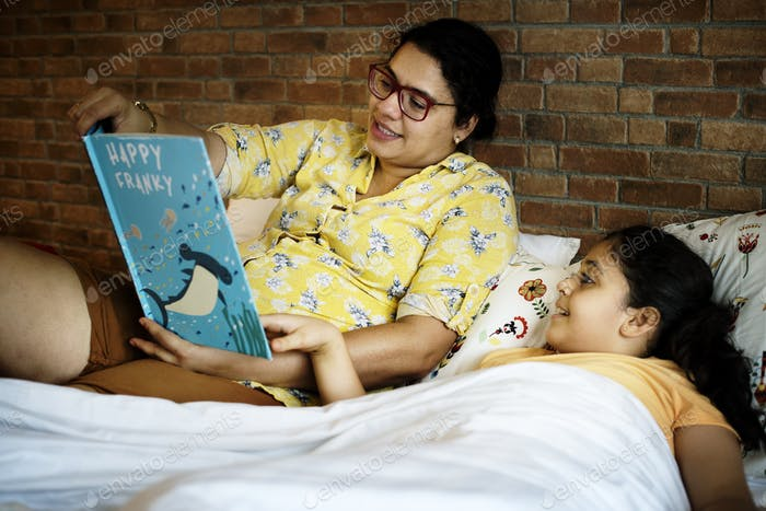 Mother reading bed time story to her daughter