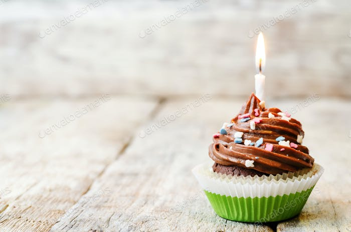 chocolate cupcake with colorful sprinkles with candles