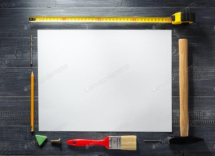 paper sheet and tools at wood