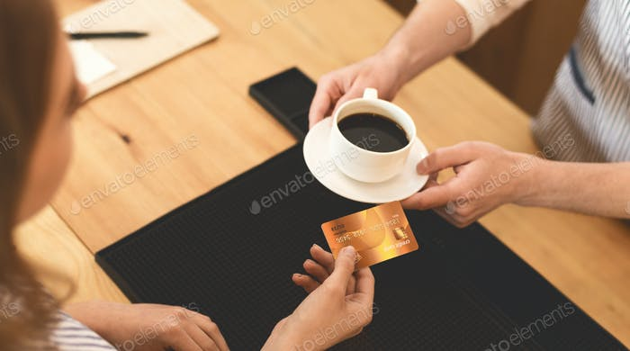 Unrecognizable Woman giving gold credit card for tasty coffee