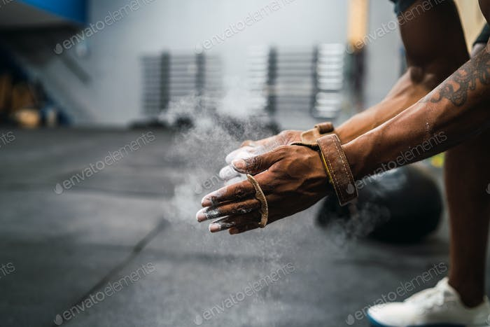 Fitness man rubbing hands with chalk magnesium powder.