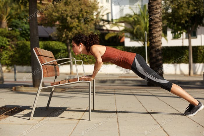 young woman doing push up against bench