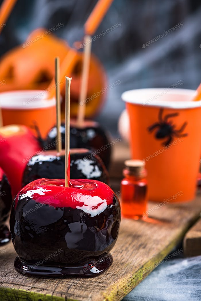 Sweet red candy apples on Halloween party table