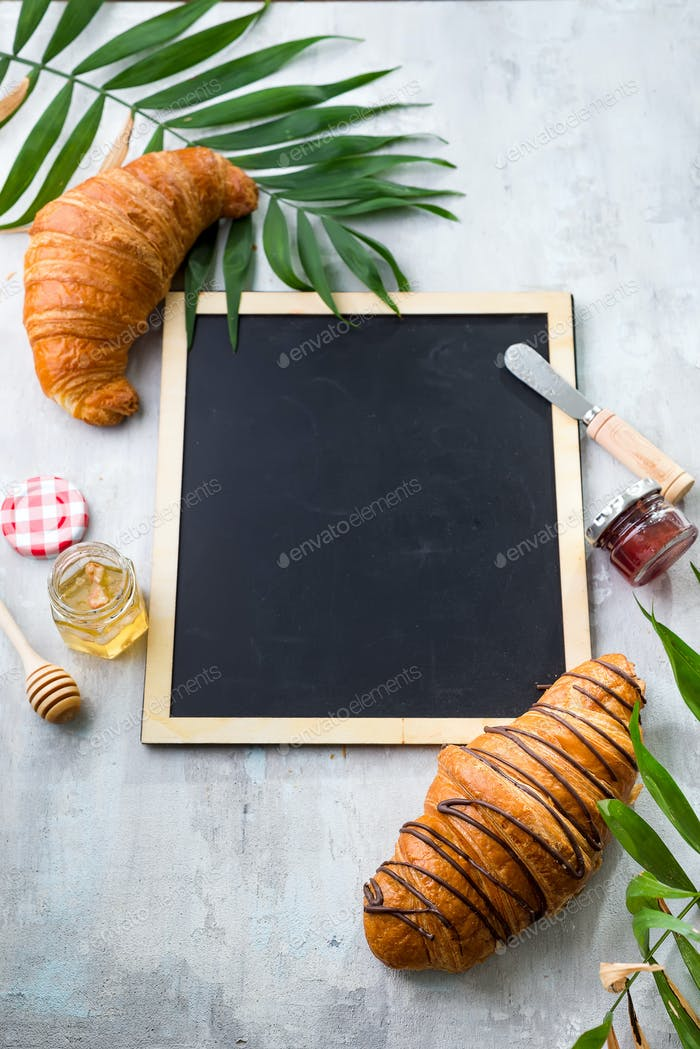 croissants, honey, jam and berries on the trip. Background of a chalkboard, palm leaf