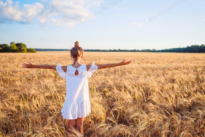 Happy cute girl in wheat field
