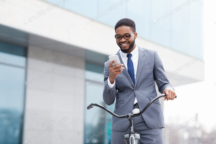 Excited businessman using phone against office building