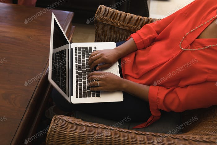 Overhead view of a senior woman using her laptop while sitting on an armchair in living room at home
