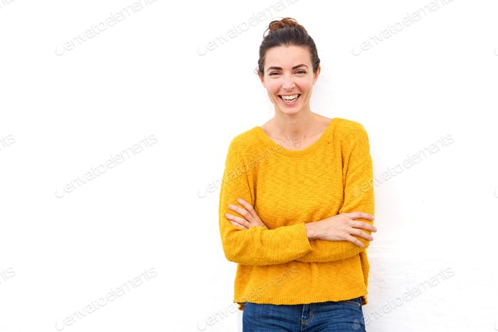 confident young woman laughing with her arms crossed on white background