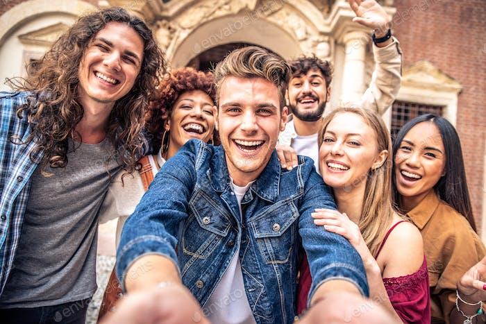 Multicultural best friends having fun taking group selfie portrait outside