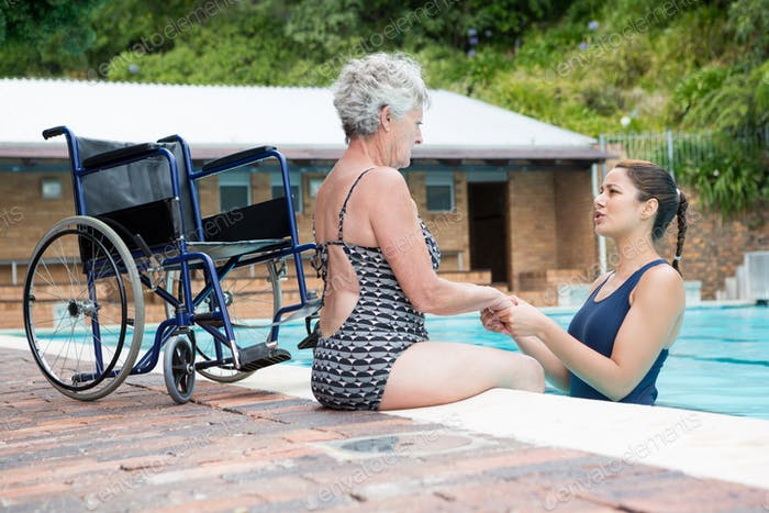 Swim coach consoling a disabled senior woman