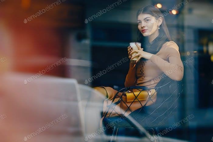 brunette girl drinking a hot beverage at a restaurant