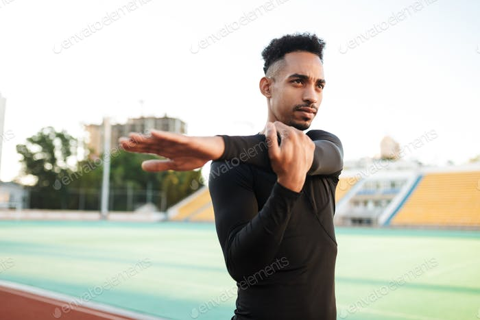 Young confident African American sportsman thoughtfully stretching on racetrack at city stadium