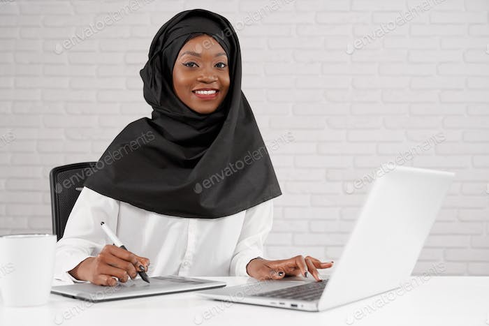 Muslim woman working in office with laptop
