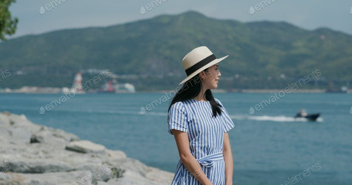 Woman look at the sea with straw hat