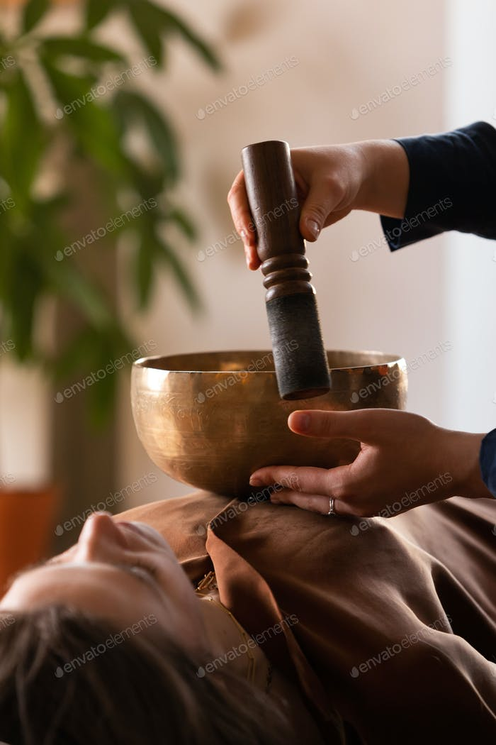 Woman making relaxing massage, meditation, sound therapy with tibetian singing bowls. Stress relief.