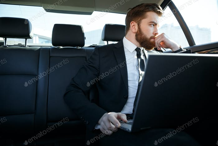 Pensive business man with laptop computer