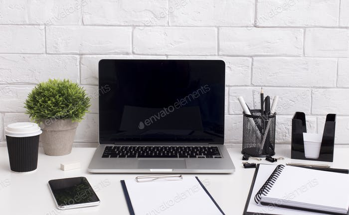 Modern laptop with blank screen for advertisement on table
