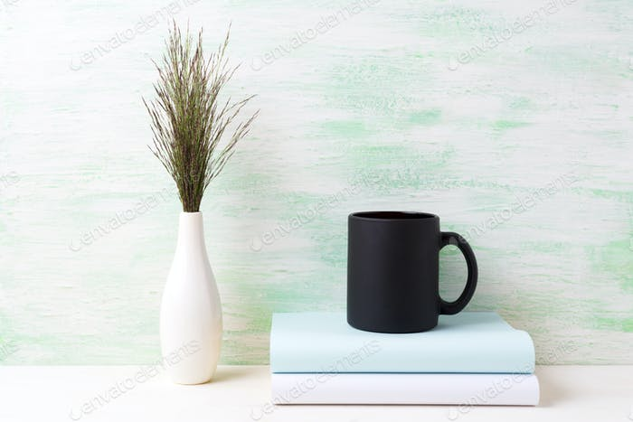 Black coffee mug mockup with dark meadow grass in vase and books