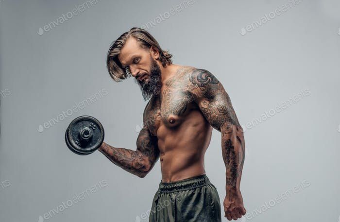 Shirtlessmale with holds dumbbell.