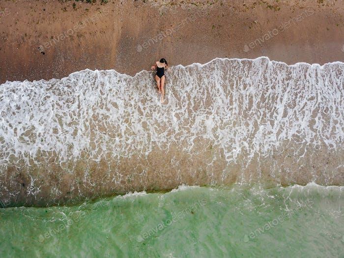 Junge asiatische Frau am Strand auf dem Sand in der Nähe der Wellen