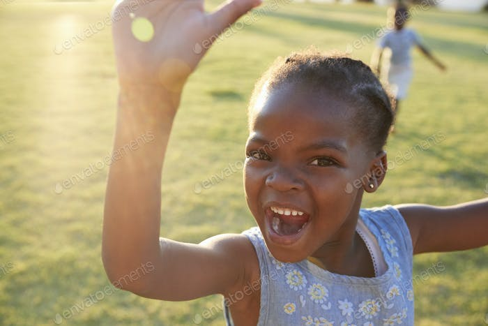 African elementary school girl waving to camera outdoors