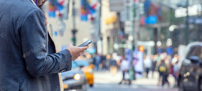 New York, Wall street. Young man in suit holding a smartphone