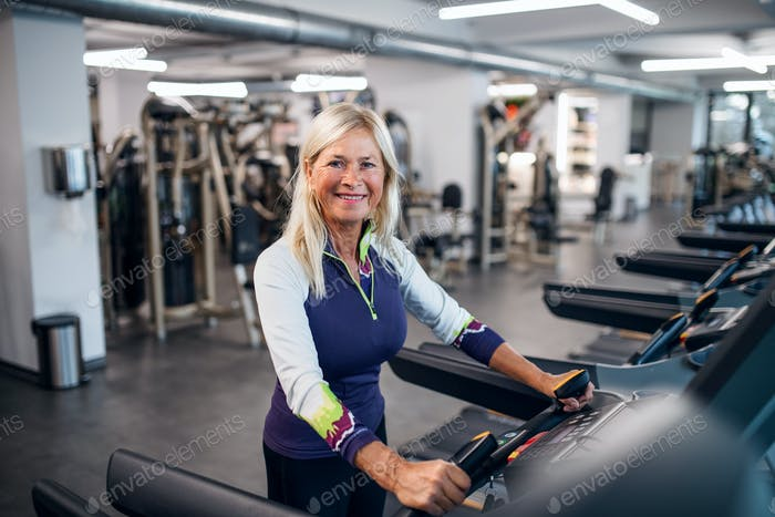 A senior woman in gym doing cardio work out exercise