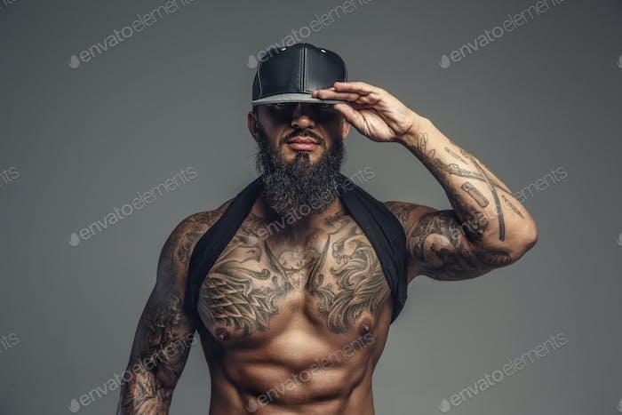 Brutal tätowierter Mann in schwarzer Mütze.
