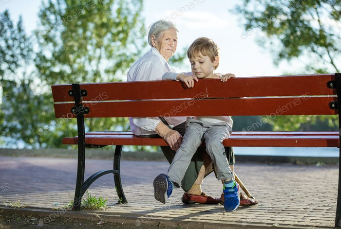 Senior woman and great grandson sitting on bench in park