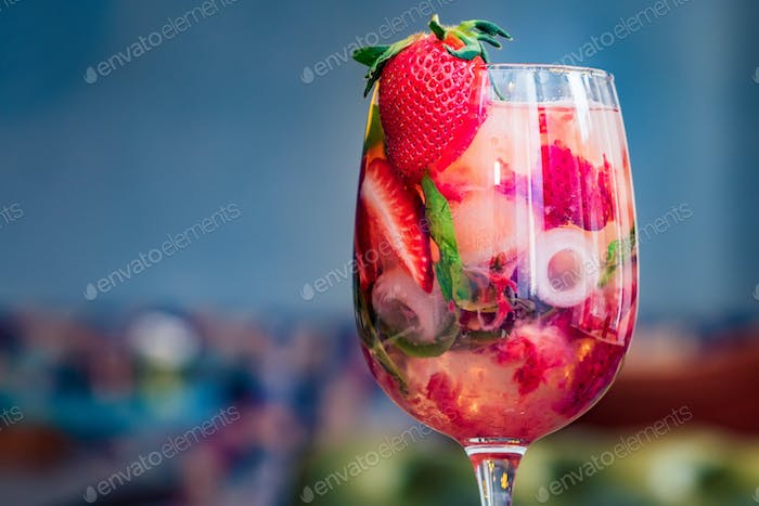 Glass with homemade srawberry mojito and berries