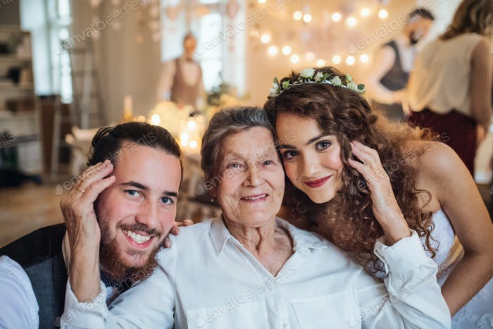 A young couple with grandmother on a wedding, looking at camera.