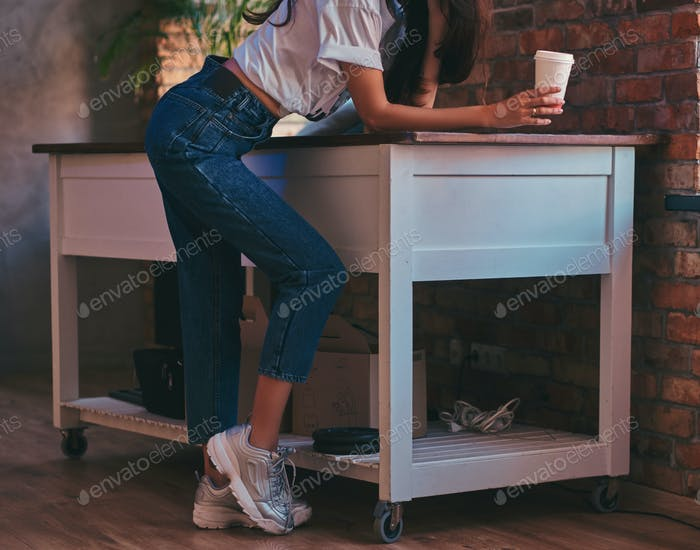 Cropped image of a cool modern girl wearing a white top and jeans in studio with loft interior.