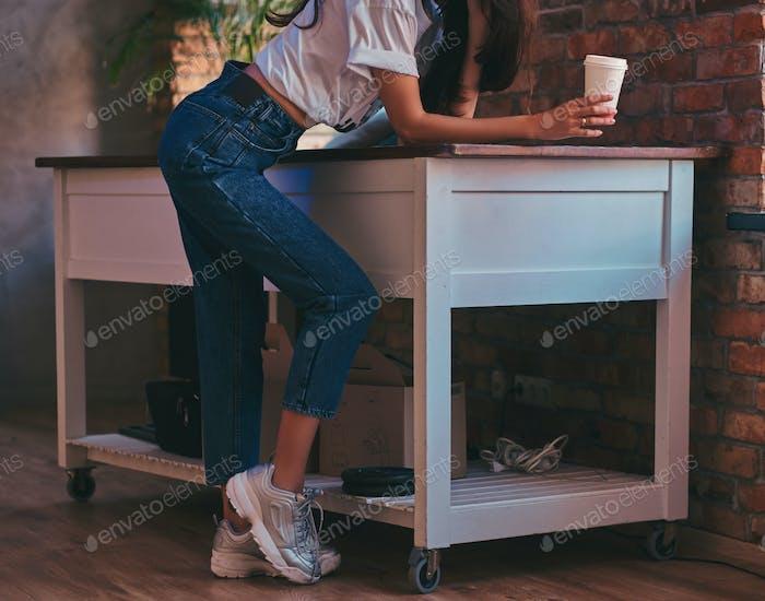 Abgeschnittenes Bild eines coolen modernen Mädchens trägt ein weißes Top und Jeans im Studio mit Loft-Interieur.