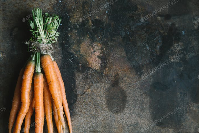 Bunch of fresh garden carrots on rusty background