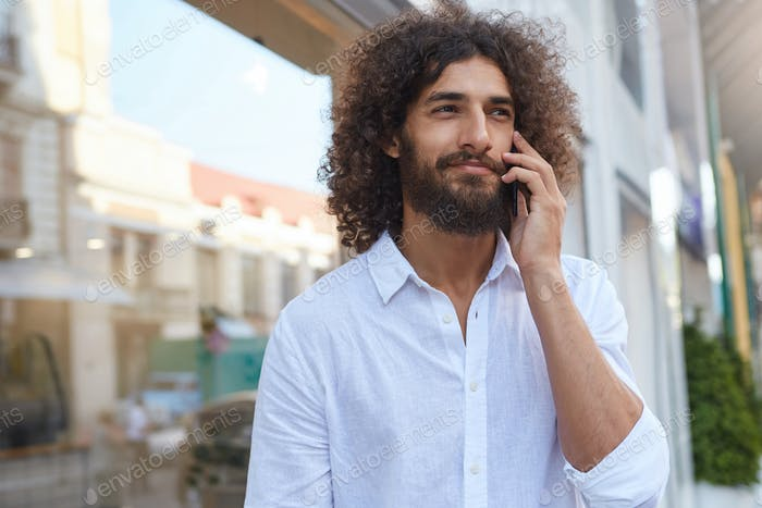 Outdoor portrait of good looking young curly male with lush beard