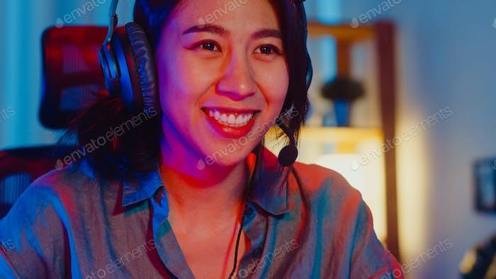 Asia profesional chica gamer desgaste auriculares participación juego de Vídeo juego de neón colorido.
