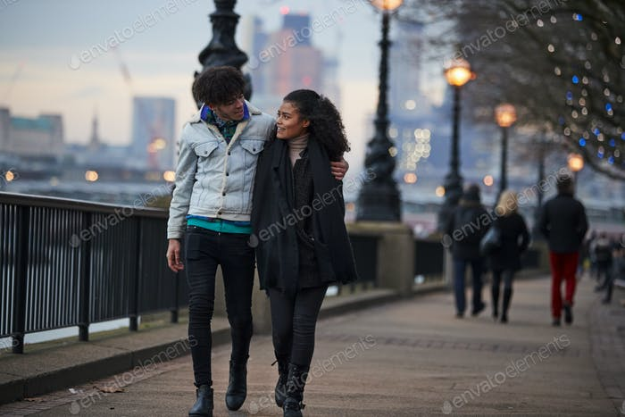 Couple Walking Along South Bank On Winter Visit To London