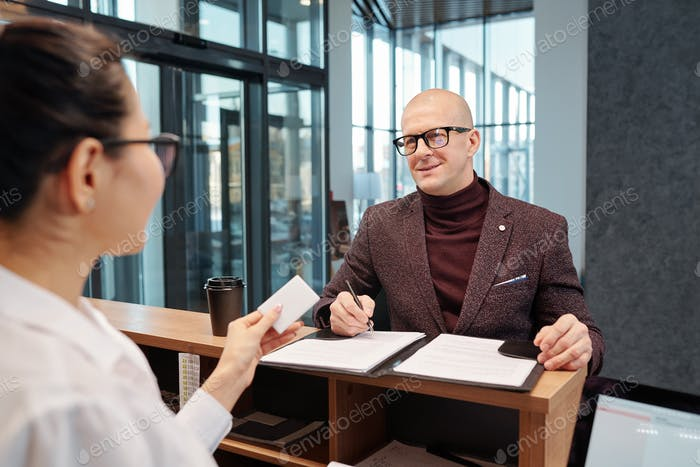 Bald businessman with pen looking at female receptionist while filling in form