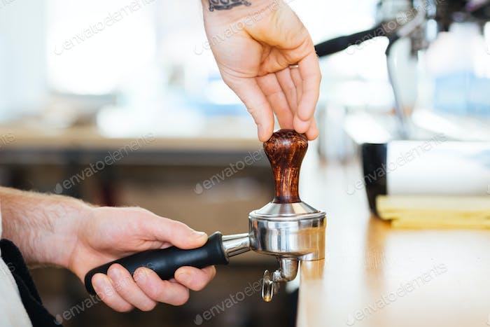 Primer plano de portafilter con temperamento utilizado por las manos baristas