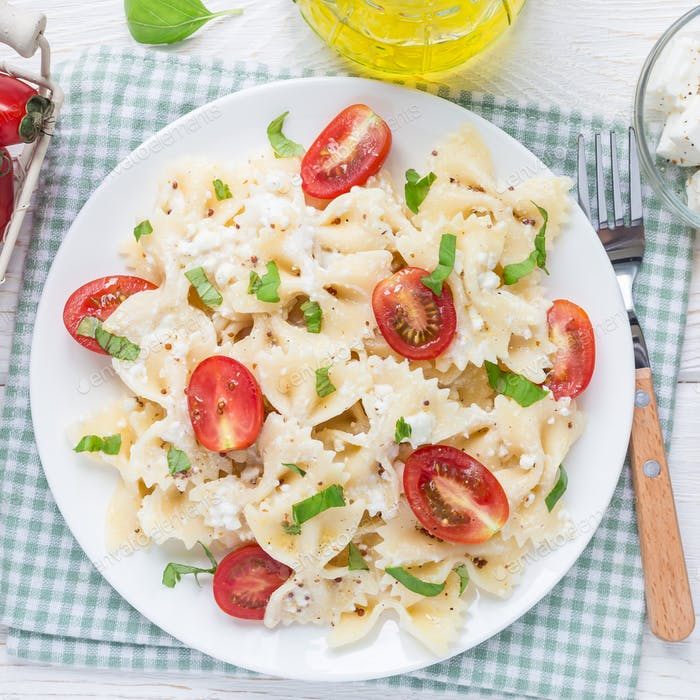 Pasta salad with tie pasta, feta cheese, cherry tomatoes, mustard and basil, top view, square format