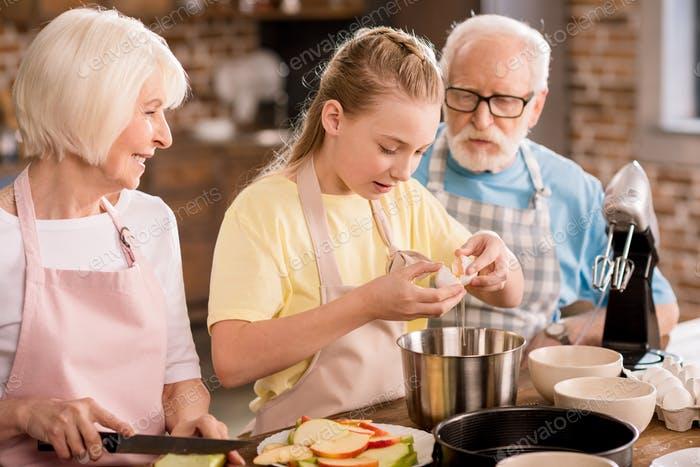 Happy grandparents with grandchild cutting apples and preparing dough for apple pie on kitchen table