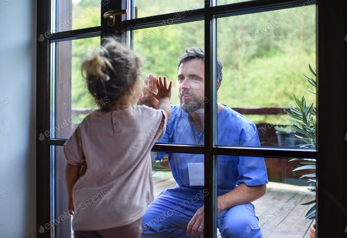 Doctor coming to see family in isolation, window glass separating them