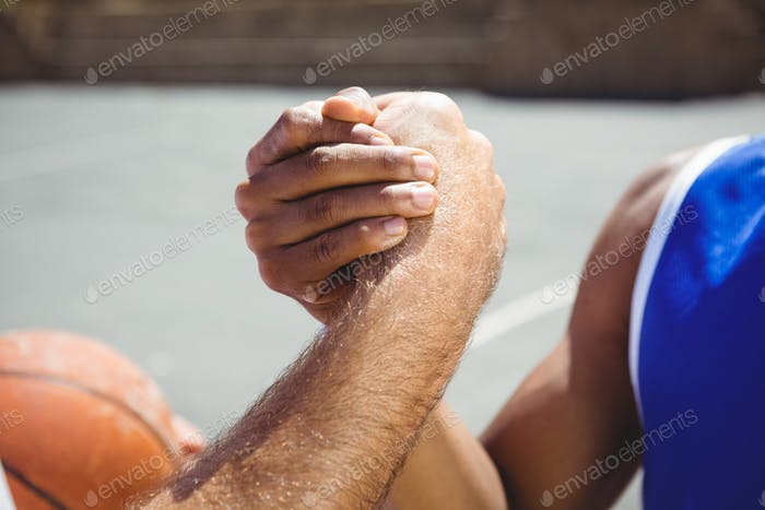 Cropped image of basketball players holding hands